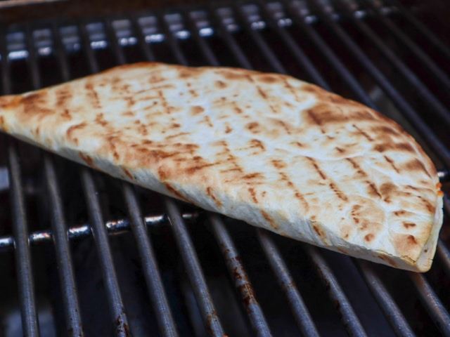 quesadilla being flipped on the grill