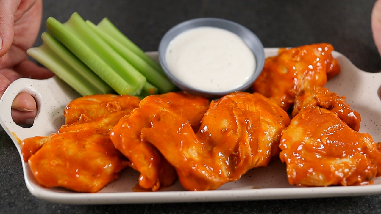 buffalo chicken thighs on a plat with celery and ranch dressing.