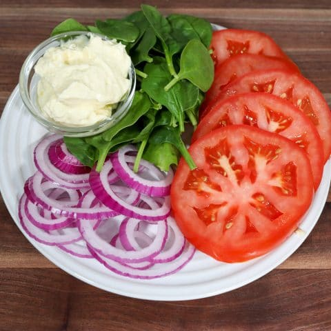 tomato, avocado mayo, onion and spinach on a plate