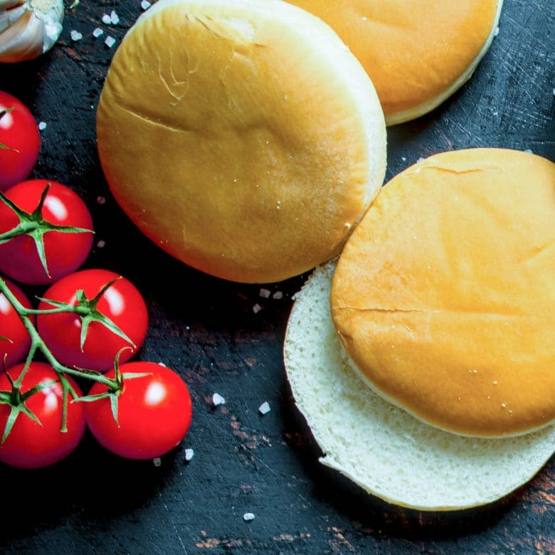 2 classic hamburger buns and a vine of grape tomatoes next to them and coarse salt sprinkled around them.