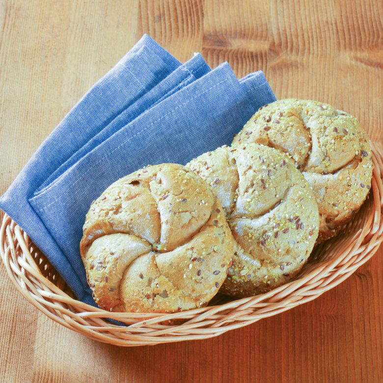 3 Kaiser rolls on a wicker basket with a blue cloth napkin.